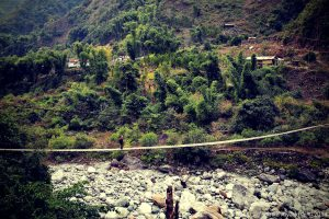 Crossing a foot bridge in Arunachal Pradesh, India, in 2014, with a Kata R-104 backpack.
